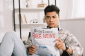 serious asian man sitting in sofa at home and reading fake news newspaper