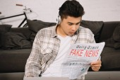 young, serious asian man in headphones reading fake news newspaper while sitting on floor near couch