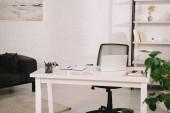 tágas, világos nappali fehér téglafal, asztallal és állványokkal