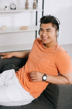 Handsome asian man smiling at camera while resting on sofa and listening music in headphones stock vector