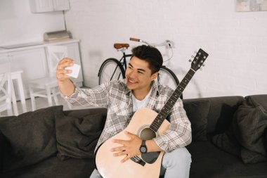 cheerful asian man taking selfie with smartphone while sitting on sofa with acoustic guitar