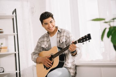 handsome, young asian man looking away while playing acoustic guitar at home