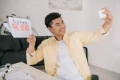 Veselý asijský muž, který si bere telefon s smartphone a současně drží noviny s falešnými zprávami