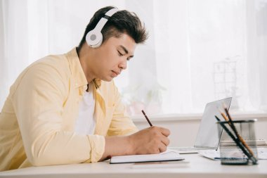 young, concentrated asian man in headphones writing in notebook white sitting at desk
