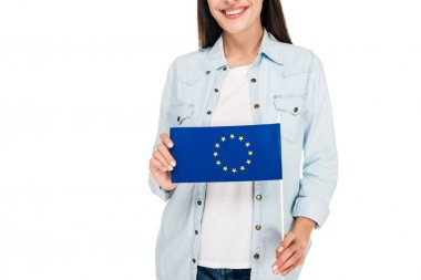 Cropped view of smiling girl in denim jacket holding flag of Europe isolated on white stock vector