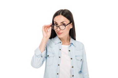 curious brunette girl in glasses and denim jacket looking at camera isolated on white