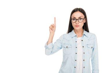 brunette girl in glasses in denim jacket pointing with finger upwards isolated on white