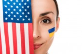 smiling young woman with painted Ukrainian flag on face holding American flag isolated on white