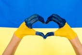 cropped view of painted hands showing heart sign on Ukrainian flag background