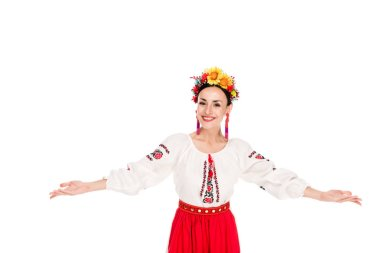 happy brunette young woman in national Ukrainian costume doing welcome gesture isolated on white