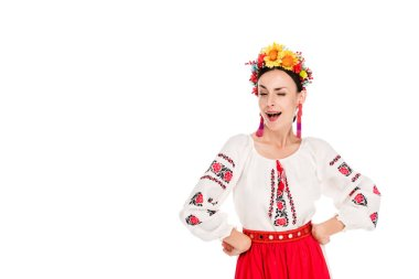Brunette young woman in national Ukrainian costume with hands on hips winking isolated on white stock vector