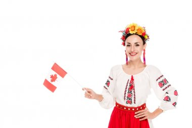 Brunette young woman in national Ukrainian costume holding flag of Canada isolated on white stock vector