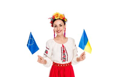 Happy brunette young woman in national Ukrainian costume holding European and Ukrainian flags isolated on white stock vector