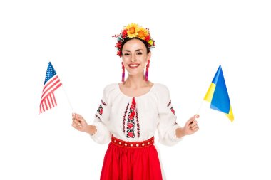 Smiling brunette young woman in national Ukrainian costume holding American and Ukrainian flags isolated on white stock vector