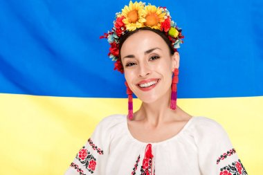 Happy brunette young woman in national Ukrainian costume with flag of Ukraine on background stock vector