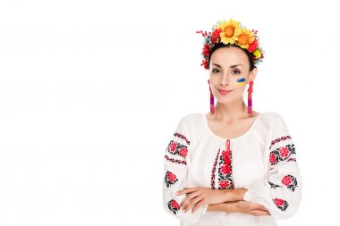 brunette young woman in national Ukrainian embroidered shirt and floral wreath with crossed arms isolated on white