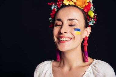 Happy brunette young woman in national Ukrainian costume with closed eyes isolated on black stock vector