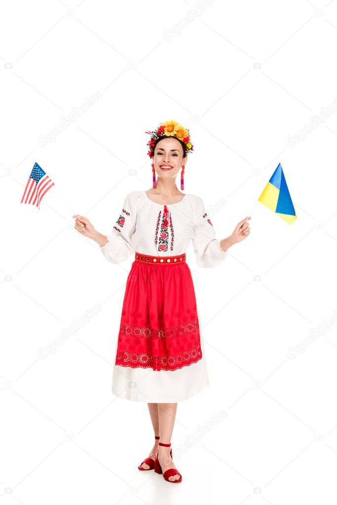 Happy brunette young woman in national Ukrainian costume holding American and Ukrainian flags isolated on white stock vector