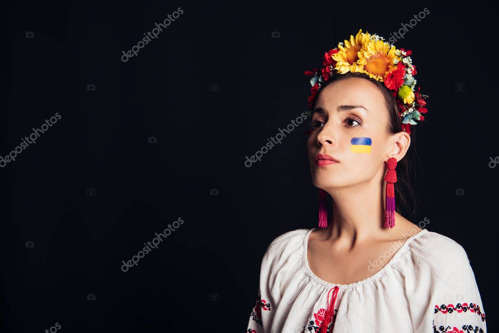 Brunette young woman in national Ukrainian costume and floral wreath looking away isolated on black stock vector