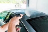 selective focus of man washing grey modern automobile outside in car wash