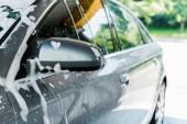selektivní zaměření zrcadla v autě s bílou pěnou ve mytí aut