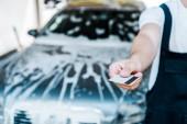 Fotografie Ausgeschnittene Ansicht eines Mannes mit Kreditkarte in der Nähe von Auto mit Schaum