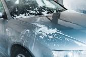 a szürke kocsi szelektív fókusza fehér habbal a Gépjárműmosó
