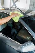 oříznutý pohled na myčku auta držící zelený hadřík a čistící vůz