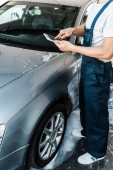 Photo cropped view of car cleaner pointing with finger at digital tablet with blank screen