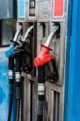 selektiver Fokus roter und blauer Zapfsäulen mit Kraftstoff auf Tankstellen