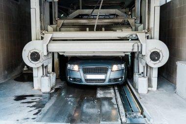 Grey vehicle with car headlights shining in car wash service stock vector