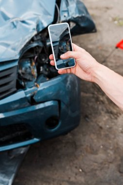 cropped view of man holding smartphone with blank screen near damaged car