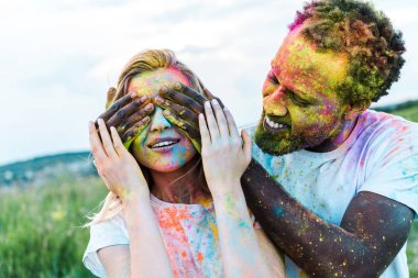 Happy african american man covering eyes of young woman with holi paints on face stock vector