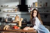 atraktivní mladá žena stojící poblíž stolu v kuchyni a dívala se na kameru