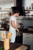 smiling muscular man in white t-shirt putting kettle on oven in kitchen