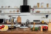 friss gyümölcsök, paprika, saláta, hal és bor konyhaasztalnál