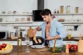 sexy muž držící pánev s rybami v kuchyni