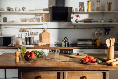 oil, fresh vegetables and cooking utensils on wooden table in kitchen