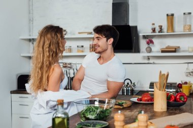 Sexy couple looking at each other near table with vegetables in kitchen stock vector
