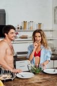 usmívající se sexy dívka, která stála u přítele a jedla salát v kuchyni