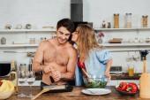 Sexy dívka líbání přítele, zatímco on ochucuje jídlo v kuchyni