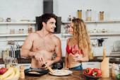 szexi lány gazdaság borospohár, míg félmeztelen barátja főzés konyhában