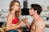Sexy Paar klimpert Weingläser mit Weißwein in Küche