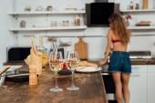 szelektív összpontosít szexi lány és asztal élelmiszer-és borospohár az előtérben