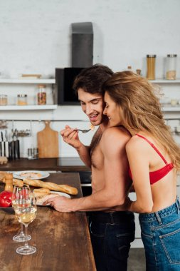 Sexy girl standing near shirtless boyfriend while he eating in kitchen stock vector