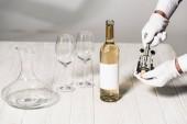 částečný pohled na číšníka v bílých rukavicích přidržovací šroub na stole blízko láhve, skleniček a džbánku
