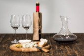 bottle of wine, wine glasses, jug, cheese, olives and bread on wooden surface