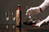 Fotografie částečný pohled na číšníka v bílých rukavicích s džbánkem vína v restauraci