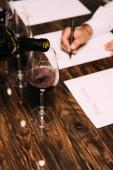 a sommelier részleges nézete a borospoharakkal ellátott asztalnál
