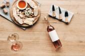 felülnézet borospohár, üveg bor, szósz, kenyér, sajt, olajbogyó, dugók és főzőeszközök a fa felületén